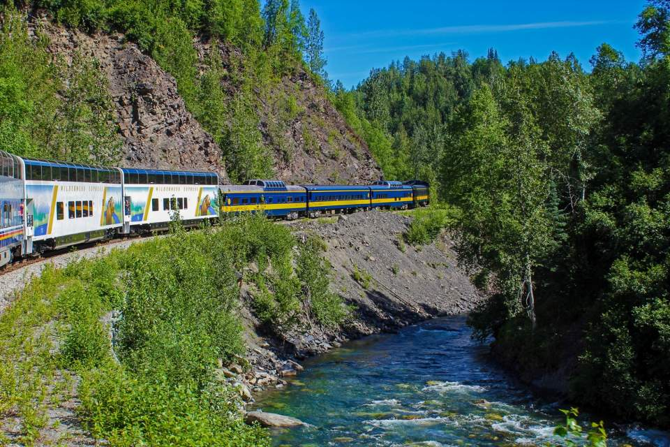 A passenger train travels along a short ridge next to a river surrounded by trees.